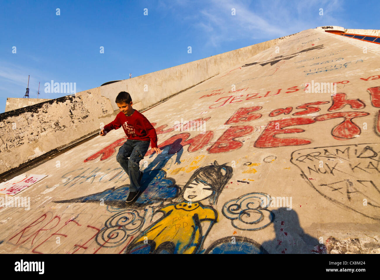 Child climbing the Pyramid, the former International Center of Culture. Tirana, Albania - Stock Image