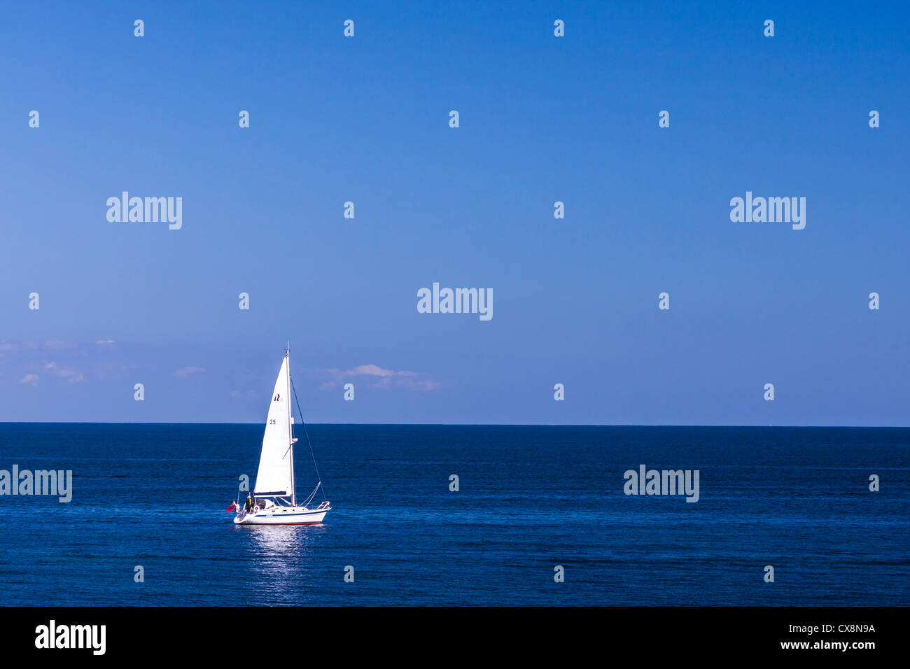Small sailing yacht in the big blue sea. Stock Photo