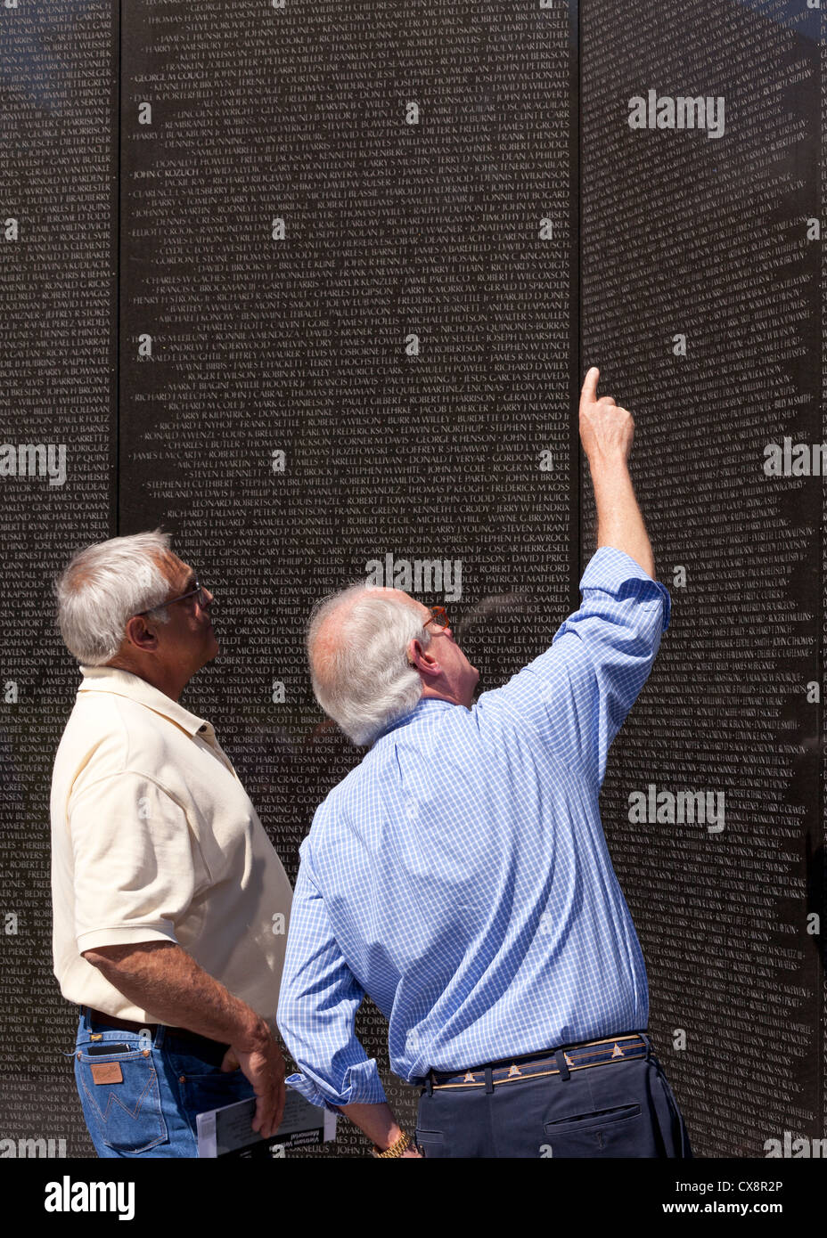 Vietnam vets point up to a name on the Vietnam War Memorial wall - Stock Image