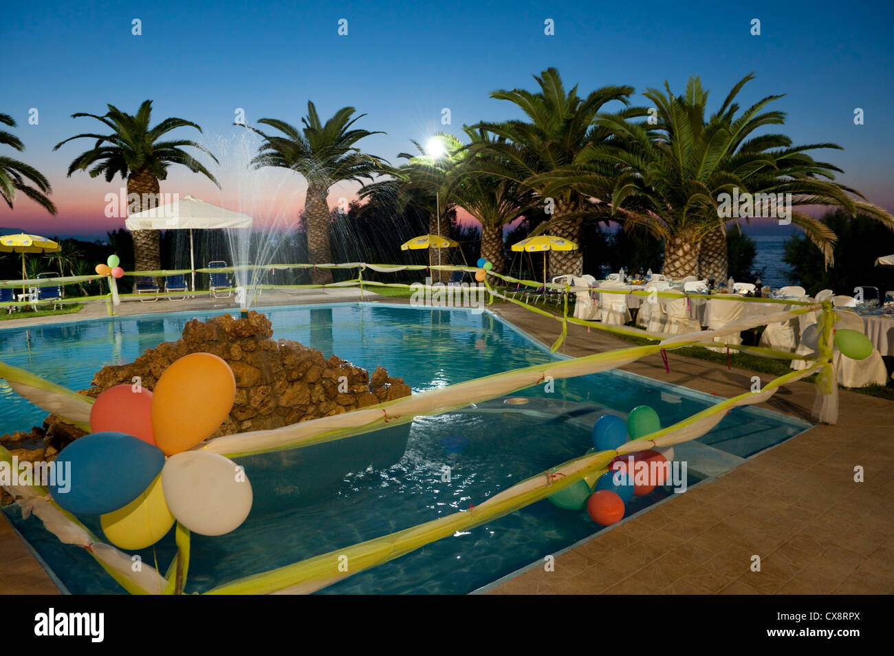 Pool side party at sunset just before the guests arrive - Stock Image