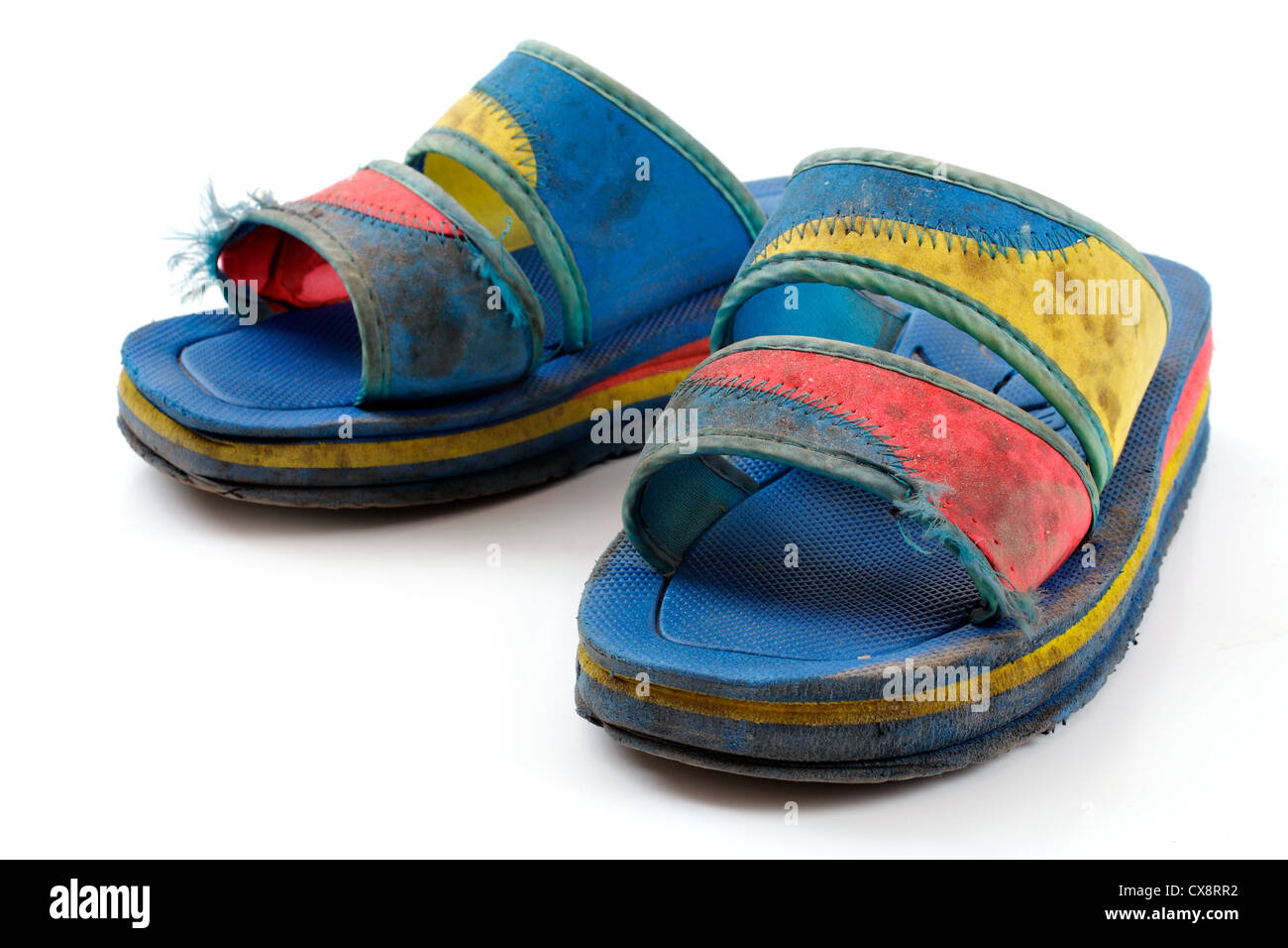 dirty old beach shoes on a white background - Stock Image