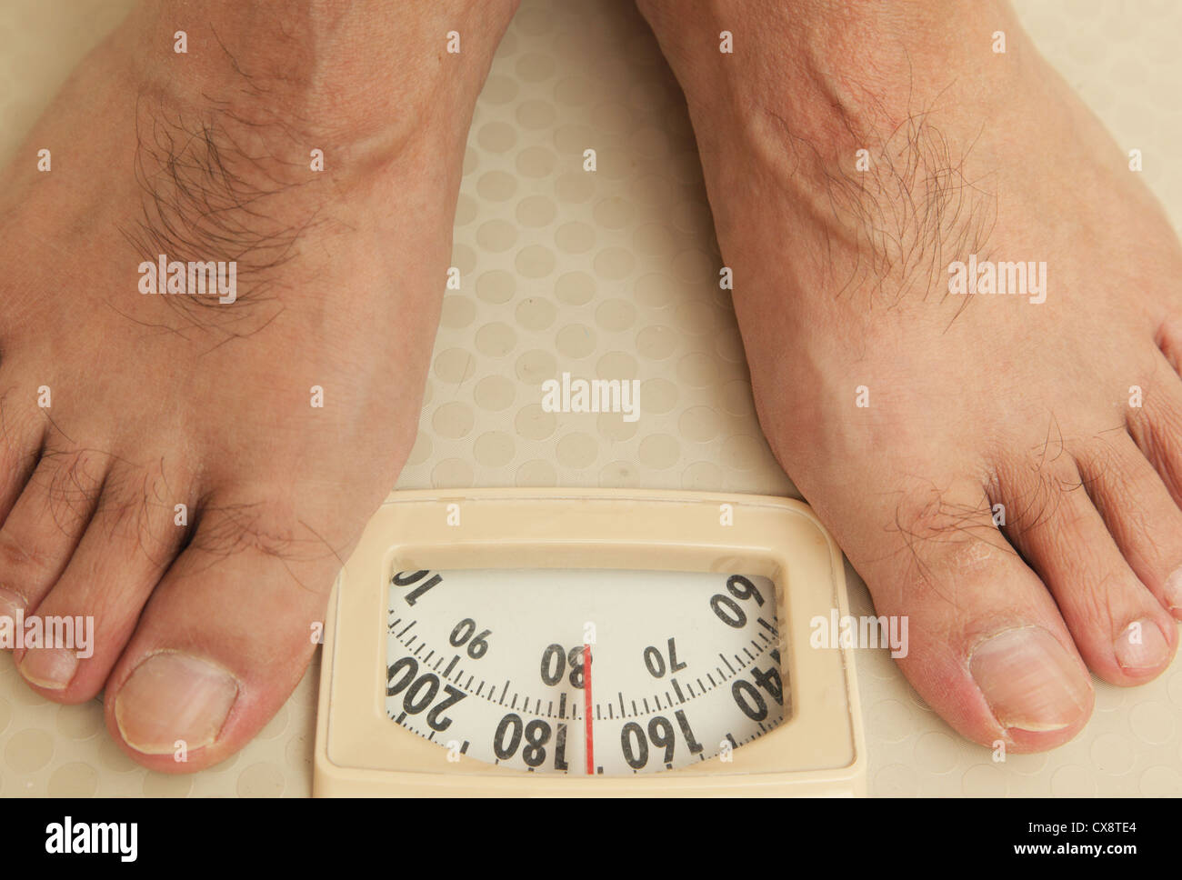 Man on a bathroom scale - Stock Image