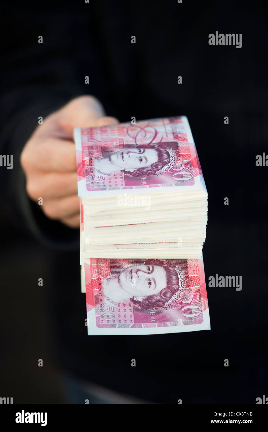 Hand holding Fifty pound notes sterling Stock Photo