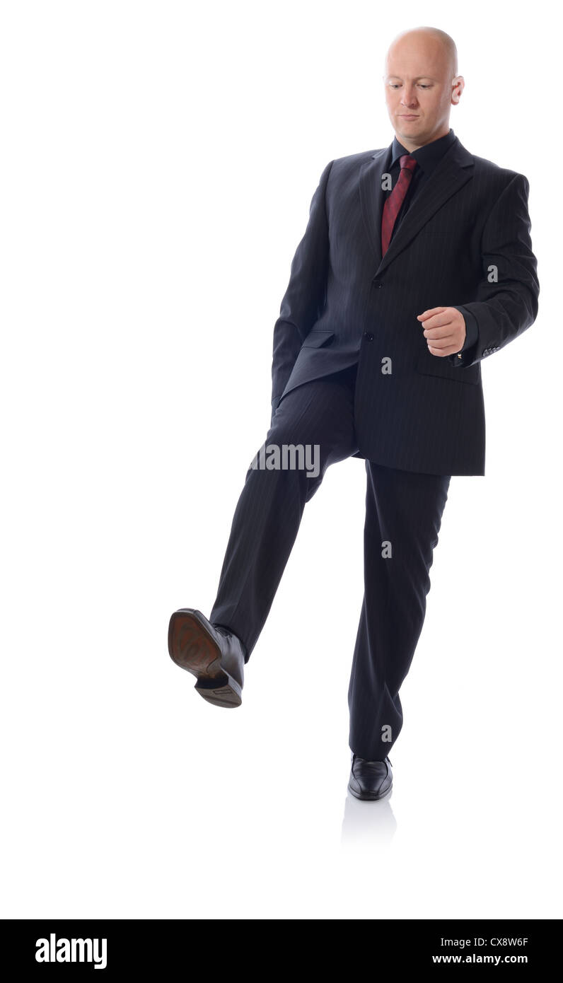 Man in suit stepping on something isolated on white - Stock Image