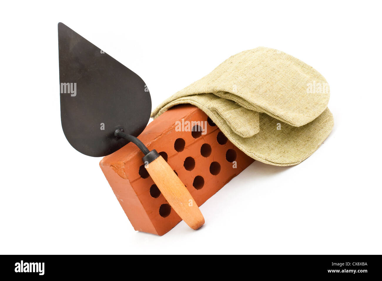 Red perforated ceramic brick, trowel and gauntlet isolated on white - Stock Image