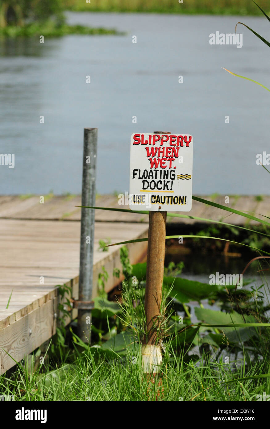 Slippery When Wet sign at dock near pond - Stock Image