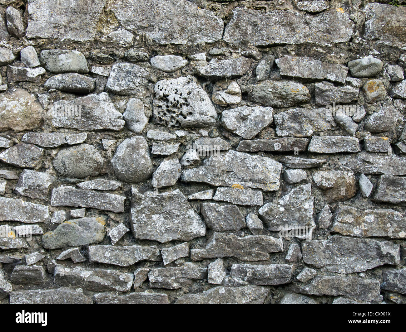 old stone wall - A section of a typical rubble-built stone wall in an Irish village, Ireland - Stock Image