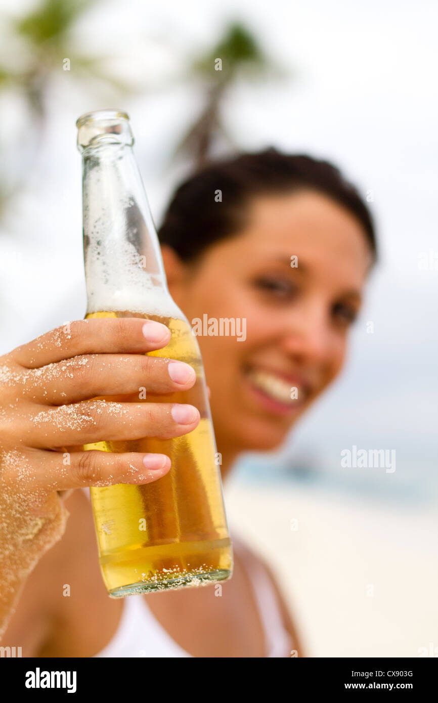 young woman with beer on beach - Stock Image