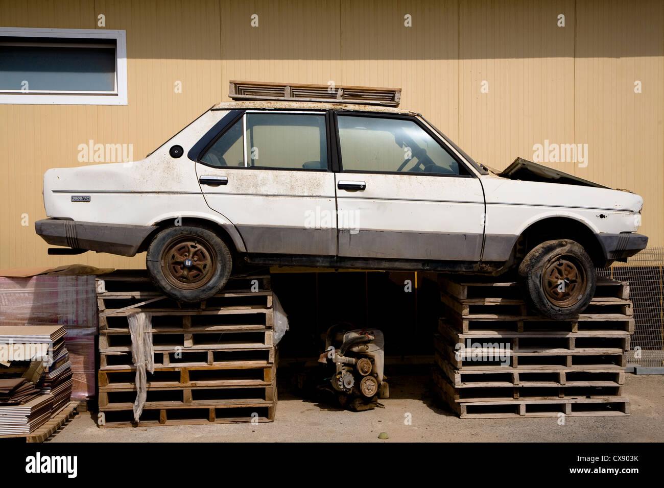 Broken down car resting on a set of pallets outside a workshop - Stock Image