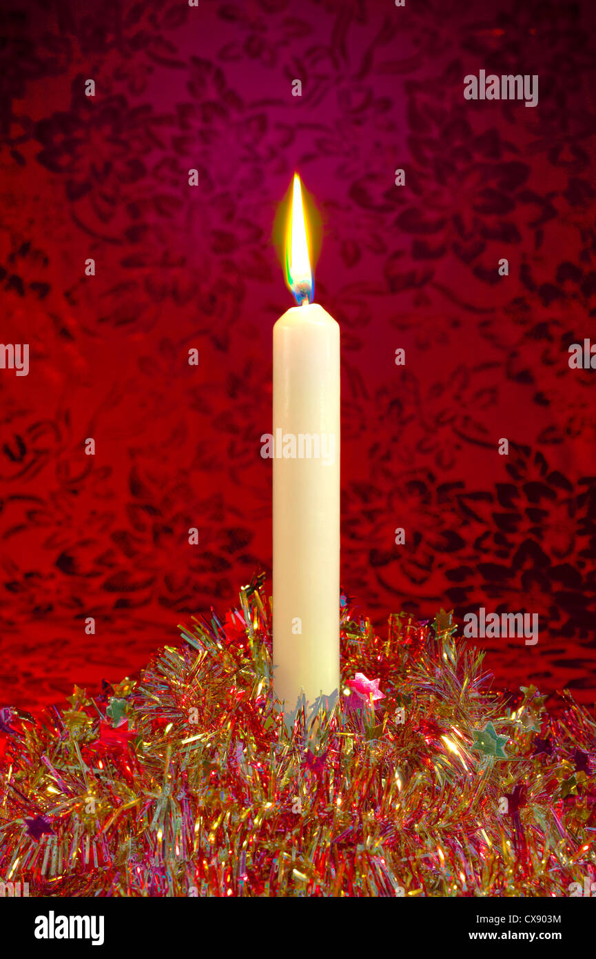 A festive Christmas candle and glittering tinsel on a red background, treated in a surrealistic manner - Stock Image