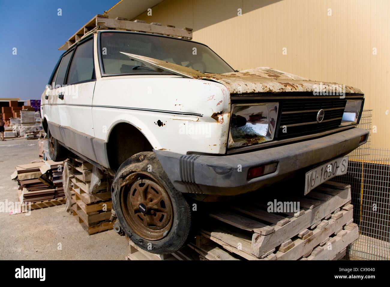 Broken down car resting on a set of pallets - Stock Image