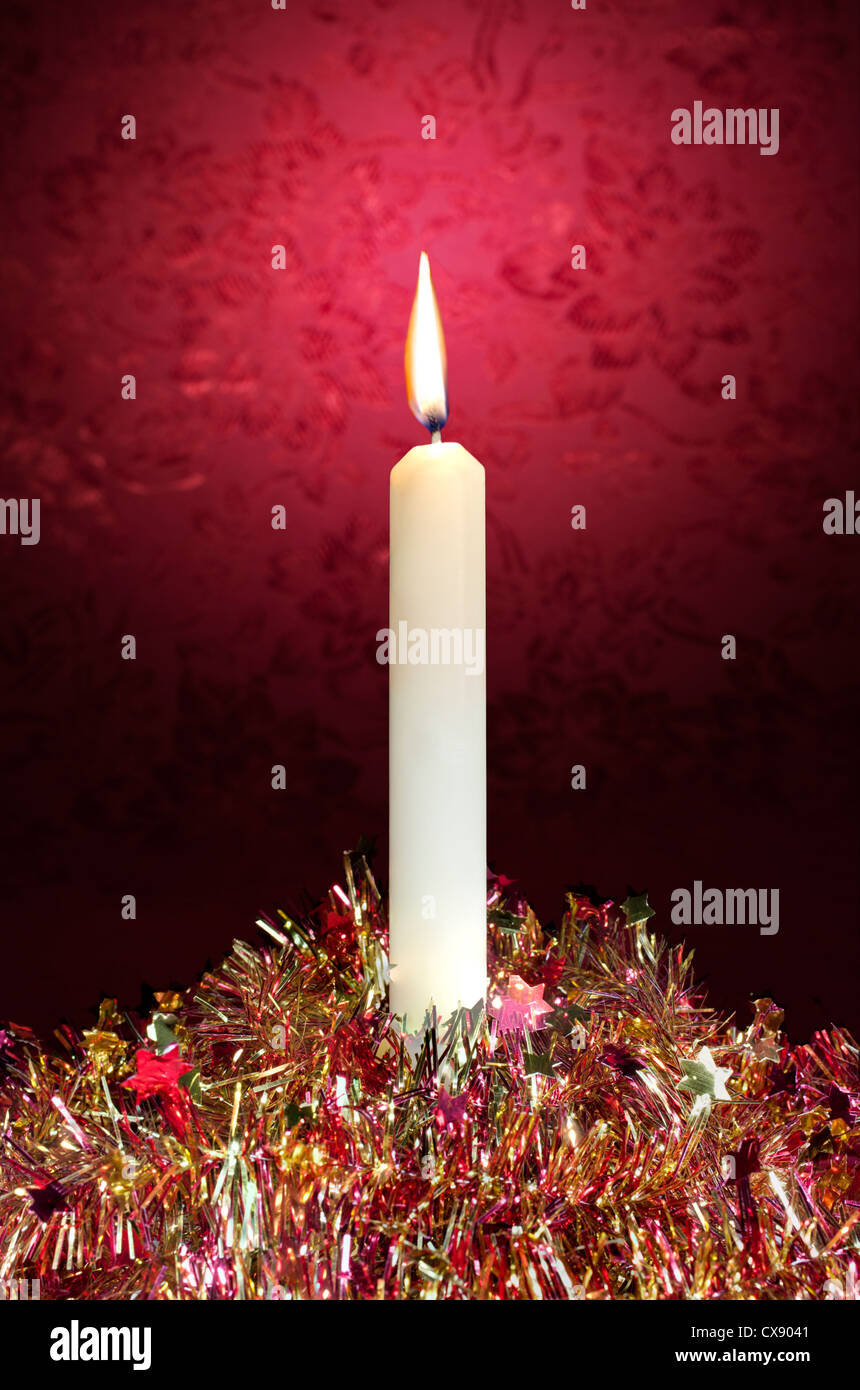 A festive Christmas candle and glittering tinsel with a red glow in the background - Stock Image