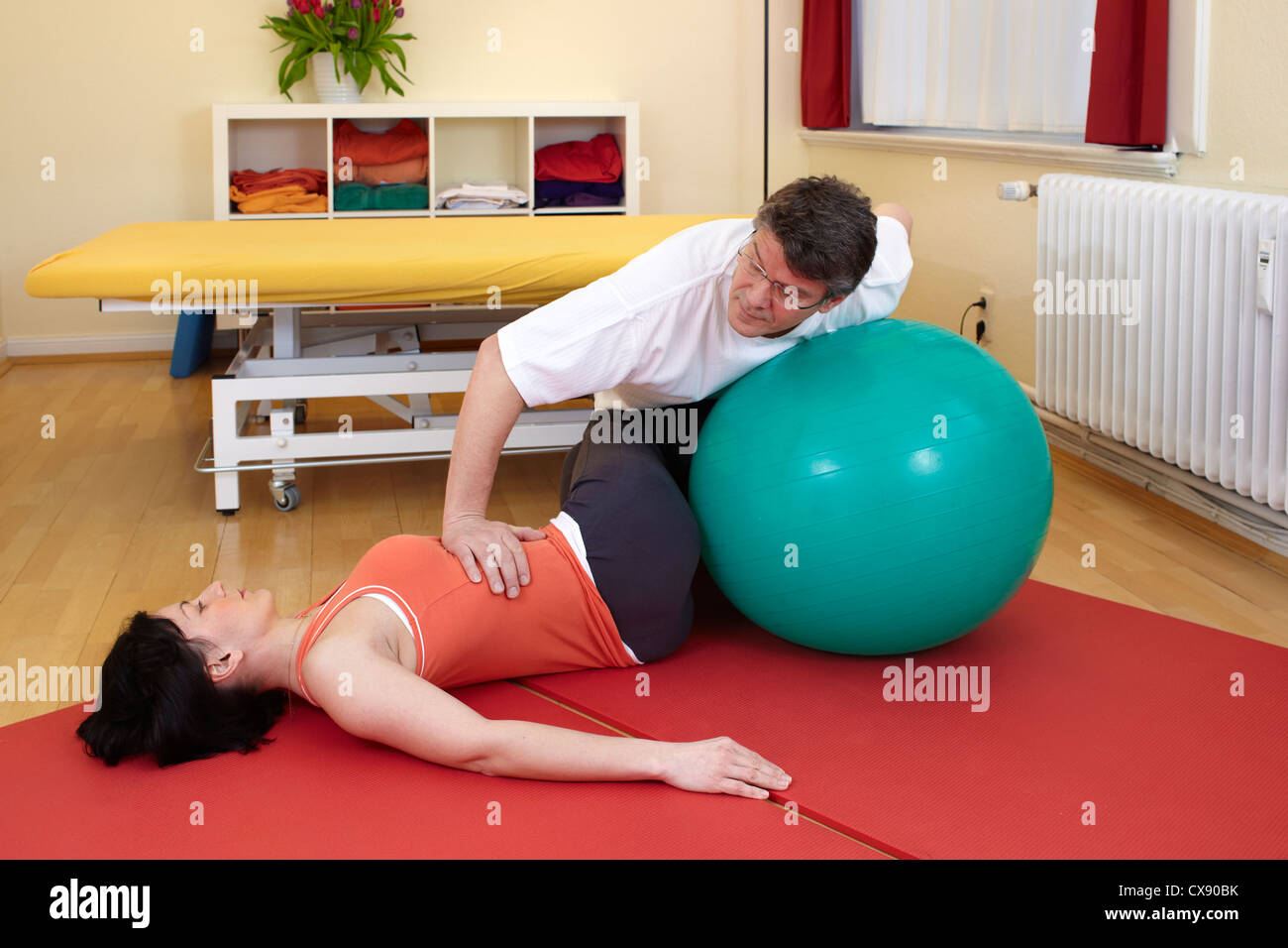adult practicing poses with exercise ball and professional physiotherapist - Stock Image