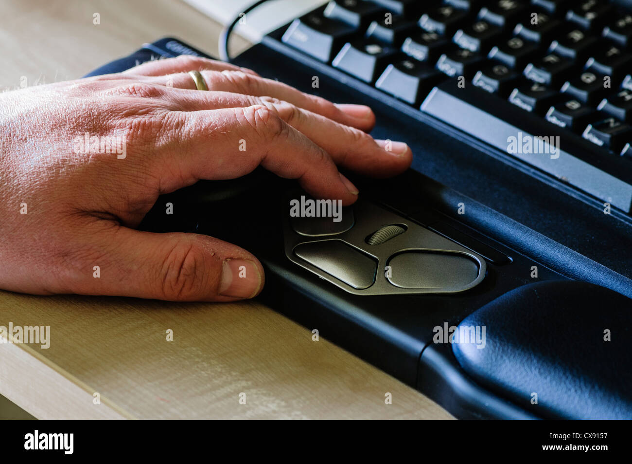 Man uses a RollerMouse Pro2 ergonomic computer mouse for people with wrist problems - Stock Image