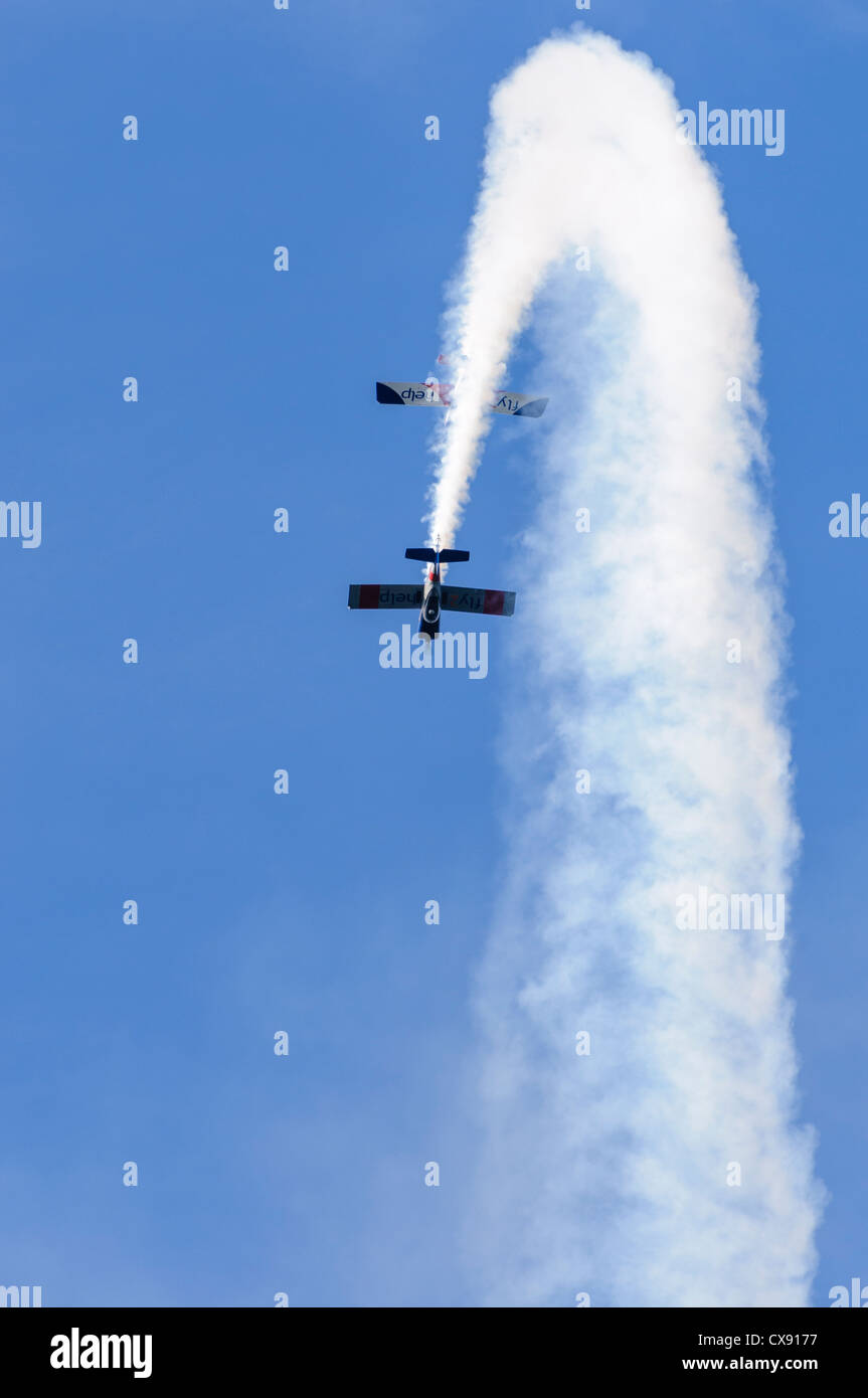 Two RV-8 aircraft (G-RVMZ G-LEXY) and performing acrobatics as the 'RV8tors' with smoke trail - Stock Image