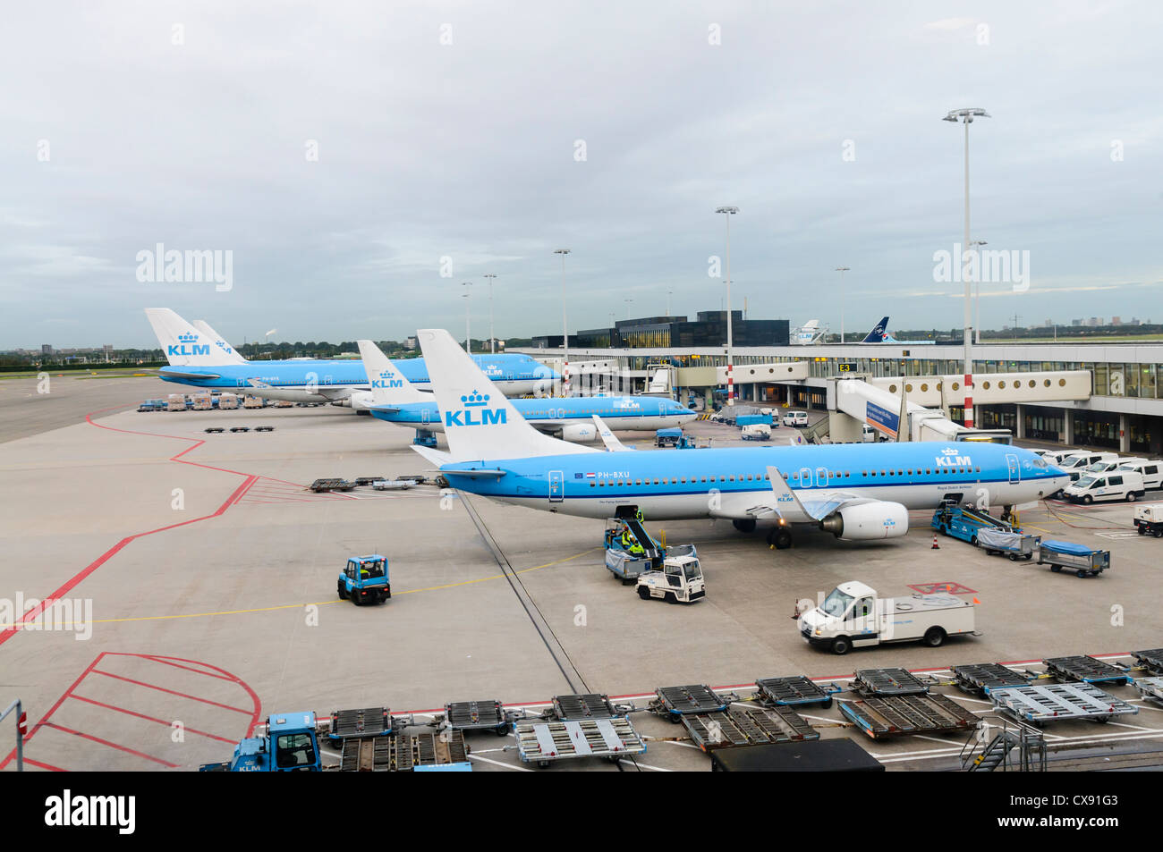 Air France KLM planes on the apron of Amsterdam Schiphol Airport with service vehicles Stock Photo