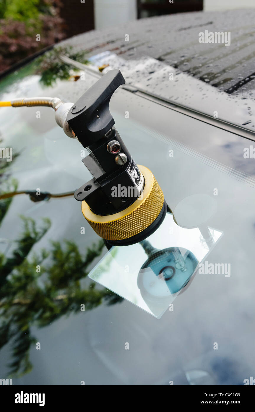 Autoglass professional repair to a chipped windscreen using vacuum pump and resin, with mirror placed behind to - Stock Image