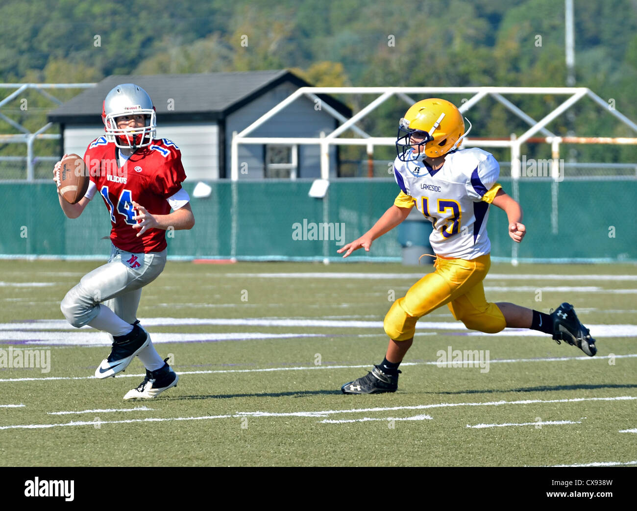 A young quarterback ready to make a pass with a player rushing to tackle. - Stock Image