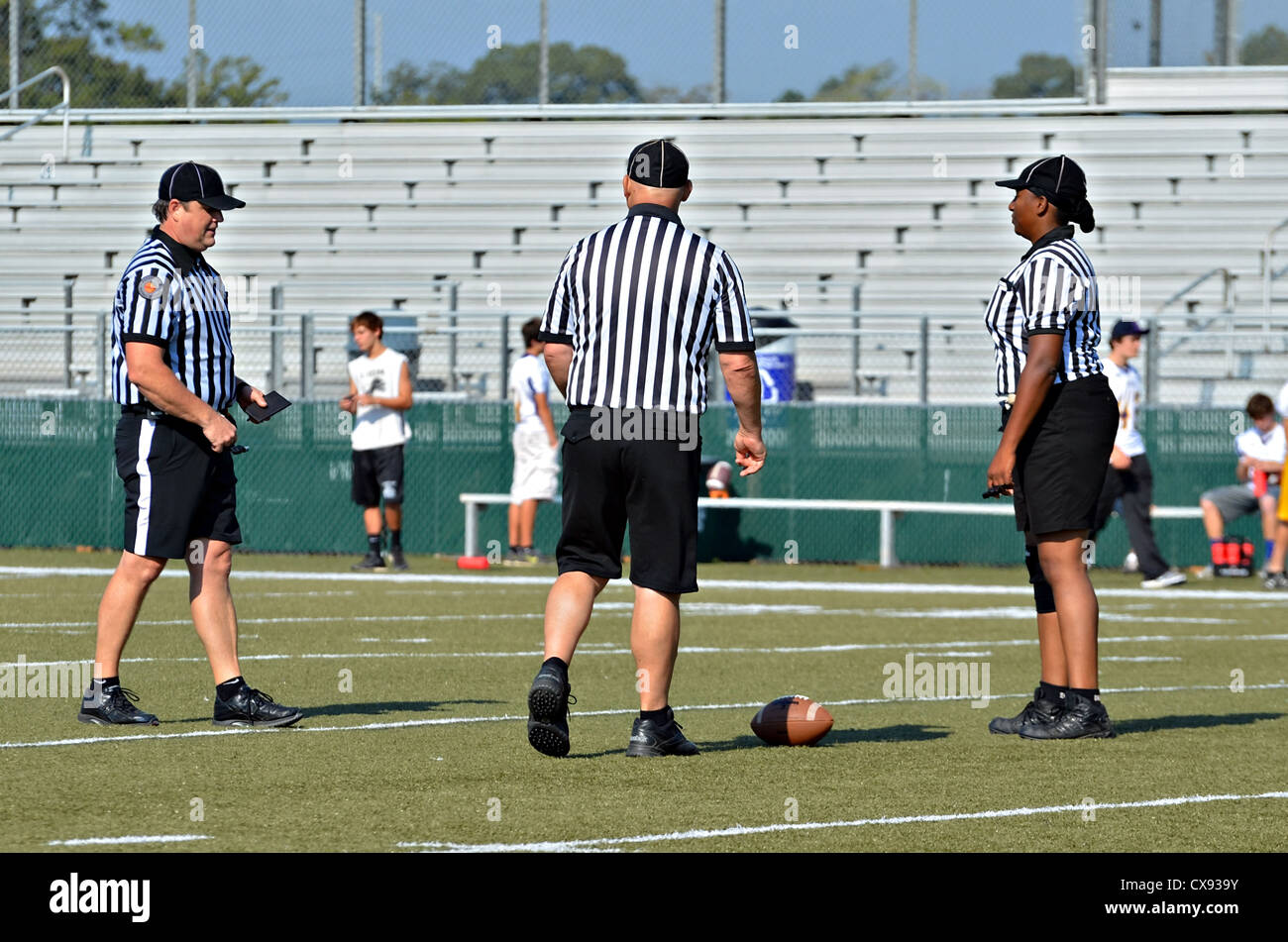Three referees, two men and a woman, discussing a play on the field during a youth football game. - Stock Image