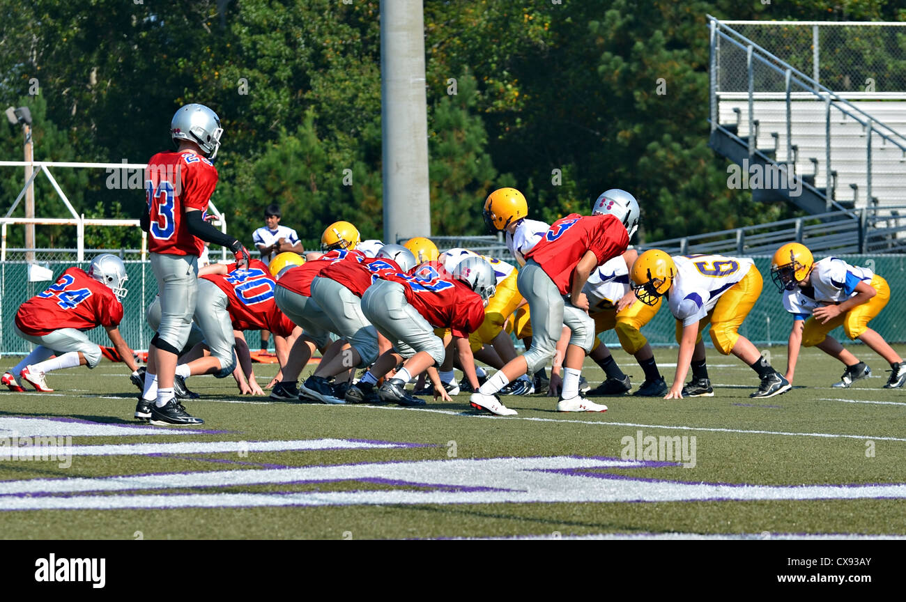 A group of 7th graders at the beginning of a football game on the line ready for the snap. - Stock Image