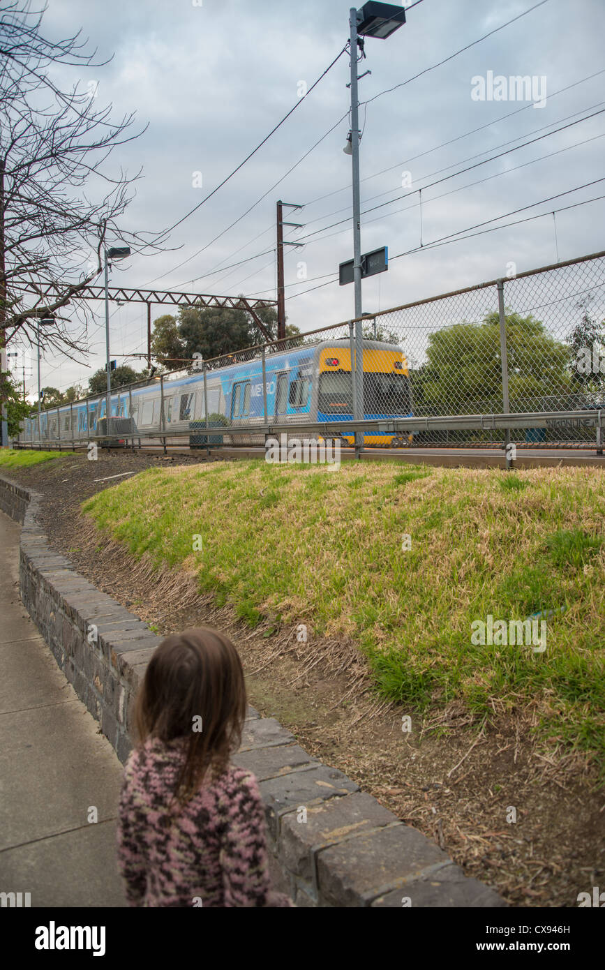 Child watching a train go past in Melbourne city - Stock Image