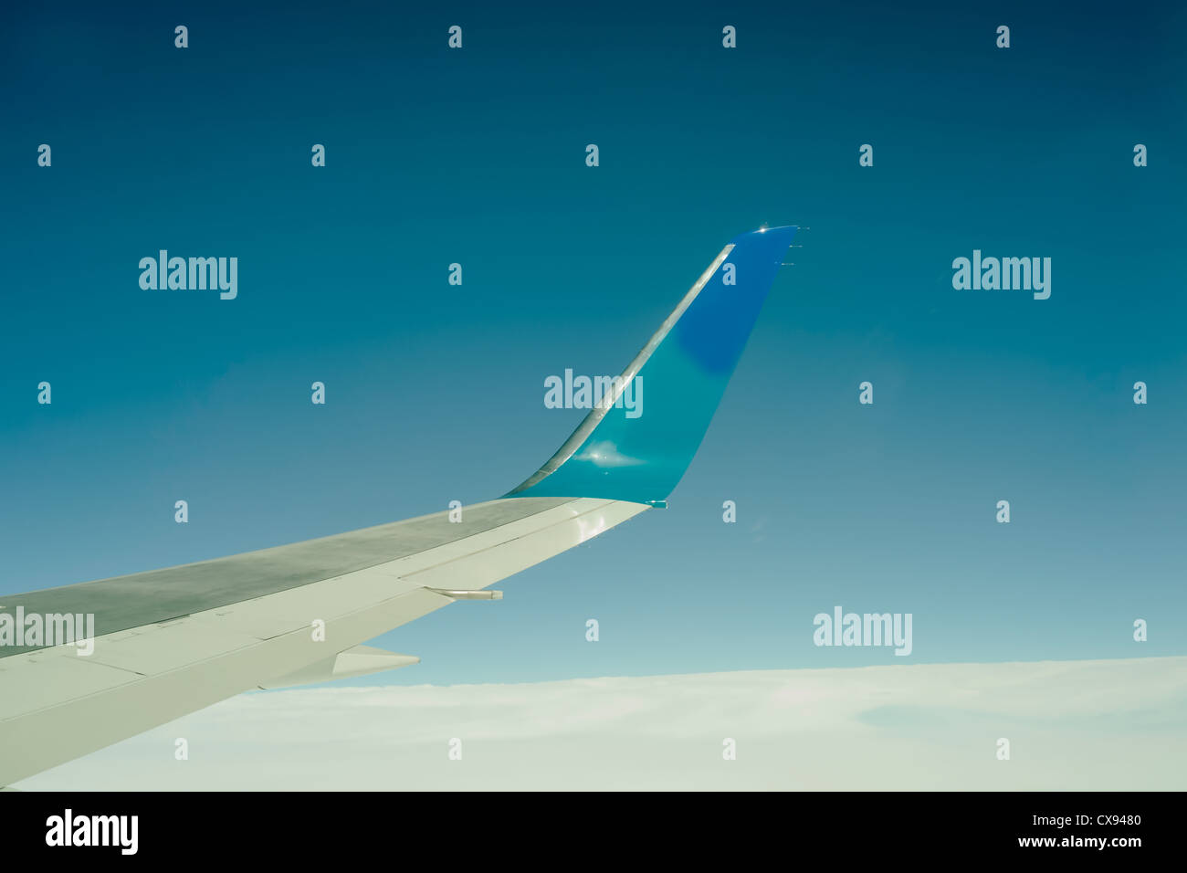 Airliner wing above the cloud and against blue sky. - Stock Image