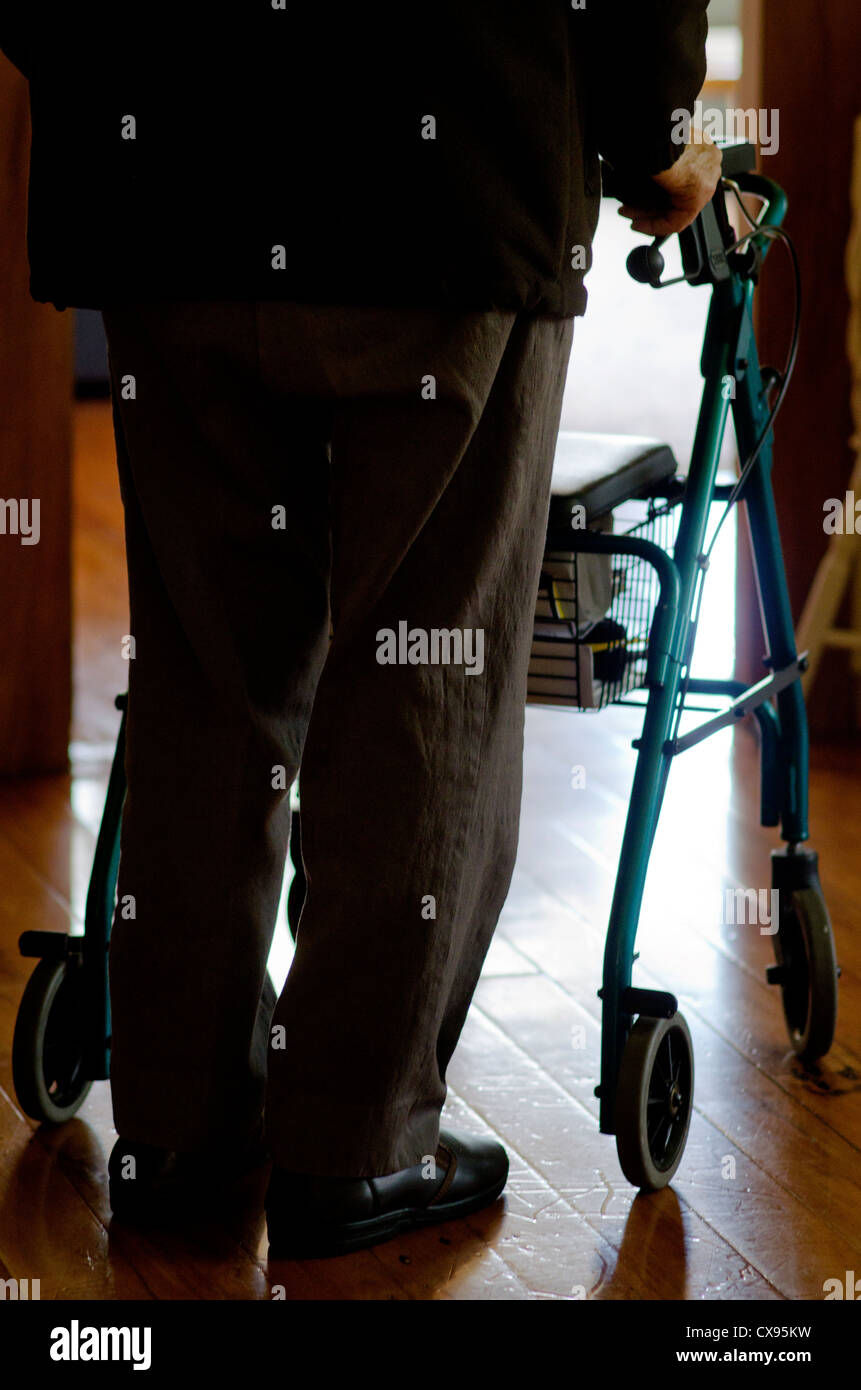 An old disabled elderly man who need additional support to maintain balance or stability while walking use a walker - Stock Image