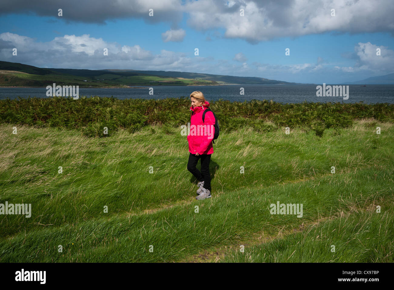 Side View Of A Woman Person Walking Through The Countryside Wearing Waterproof Clothing and A Rucksack - Stock Image