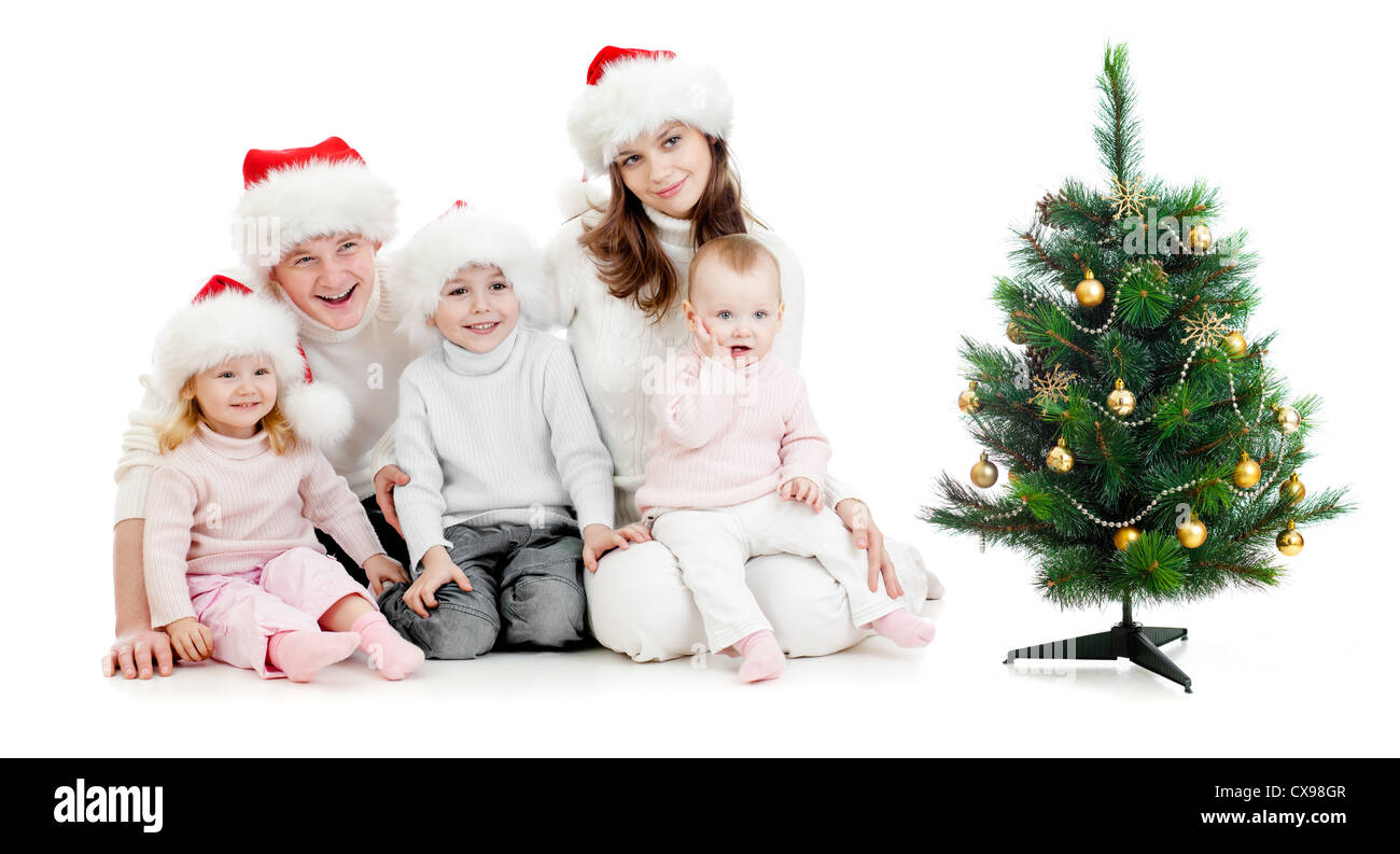 happy family in Snta's hats near christmas tree isolated on white - Stock Image