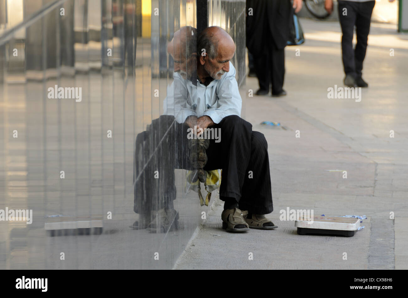 Old man trying to make money with his weight scale in uptown Tehran. - Stock Image