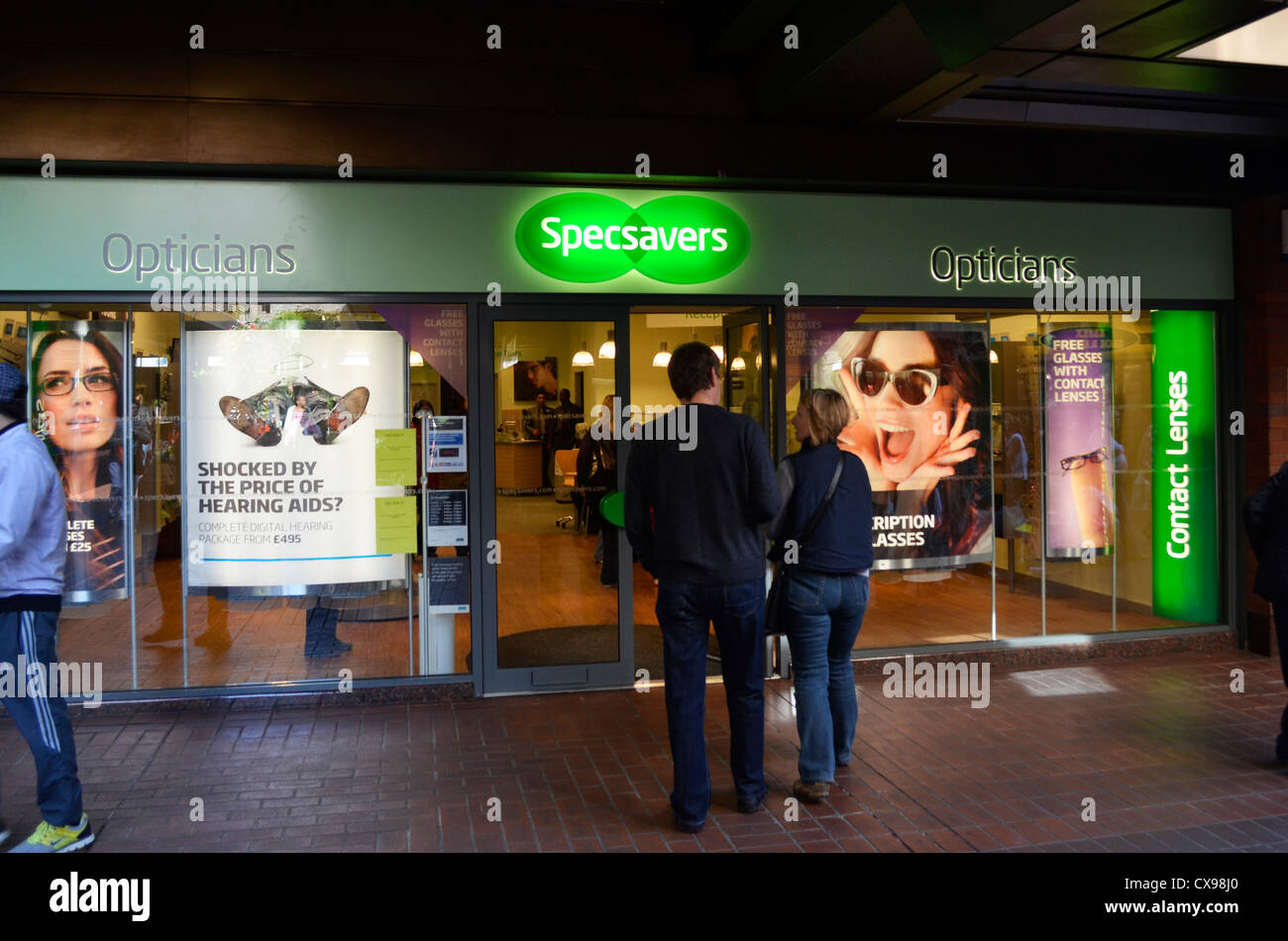 Picture shows couple walking into a Specsavers store in Enfield town Stock Photo