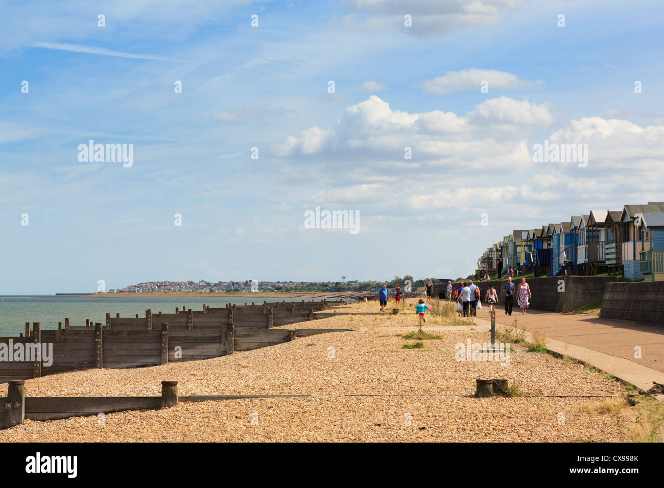 Whitstable seafront promenade along Saxon Shore Way with beach huts and shingle beach in Tankerton Bay on north Stock Photo