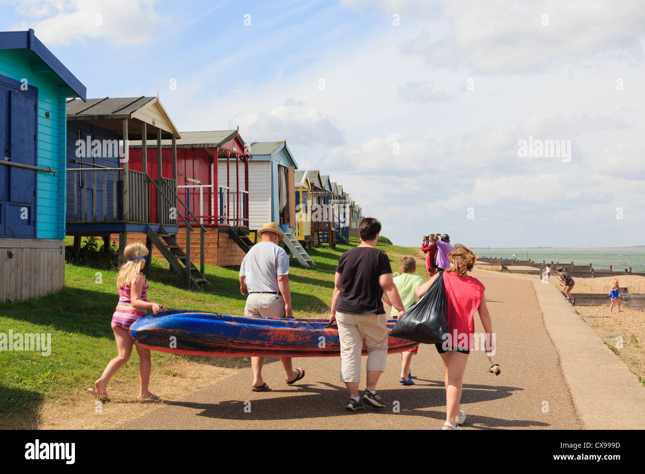 People on Whitstable seafront promenade with beach huts on north Kent coast Thames estuary in summer. Tankerton - Stock Image
