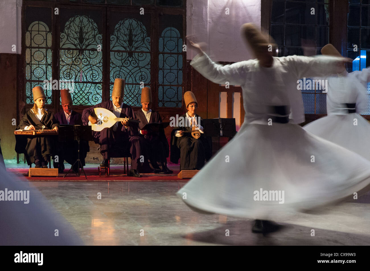 Whirling dervishes and musicians perform tin the event hall of Sirkeci Train Station on October 21, 2005 in Istanbul, - Stock Image