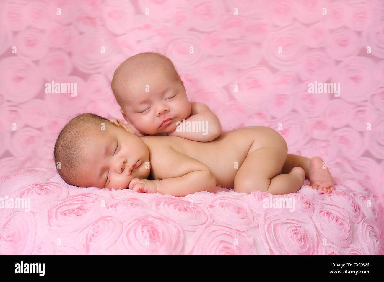 09617090c304 Fraternal twin newborn baby girls sleeping on pink rose fabric Stock ...