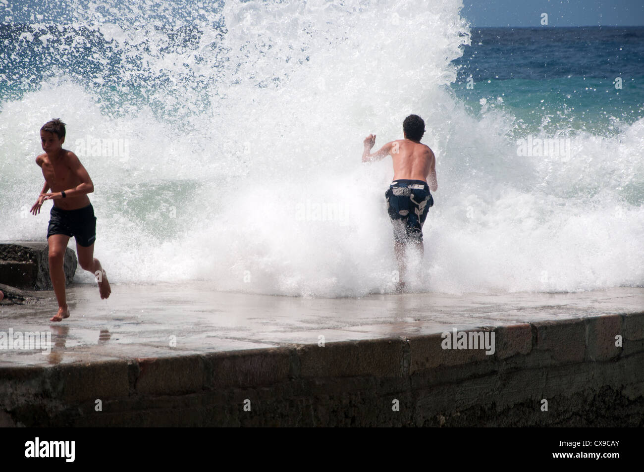 Wave dodging in Vernazza, Italy - Stock Image