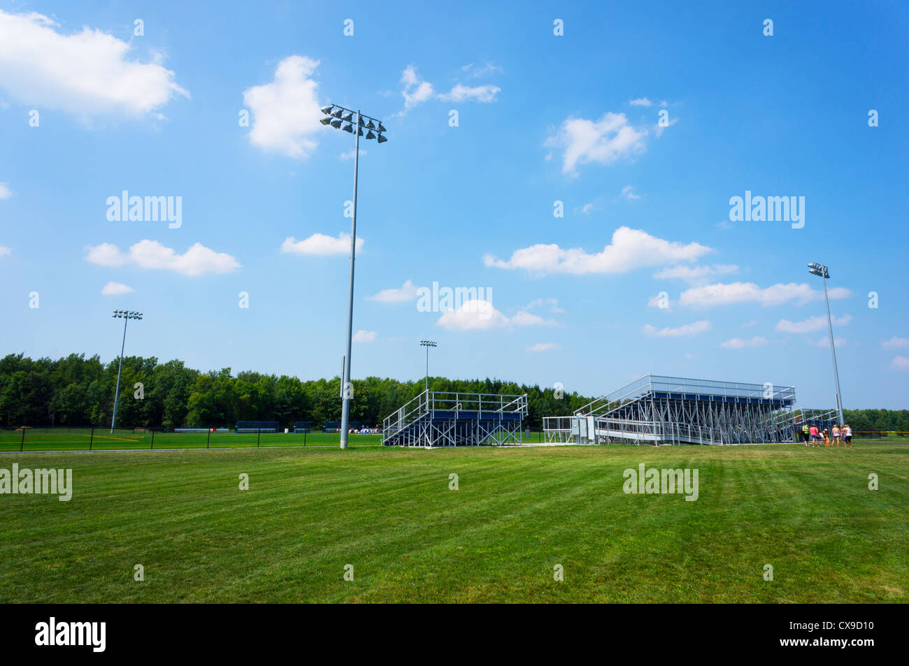 Wide angle shot of a college football (soccer) field with stands (bleachers) and floodlights. - Stock Image