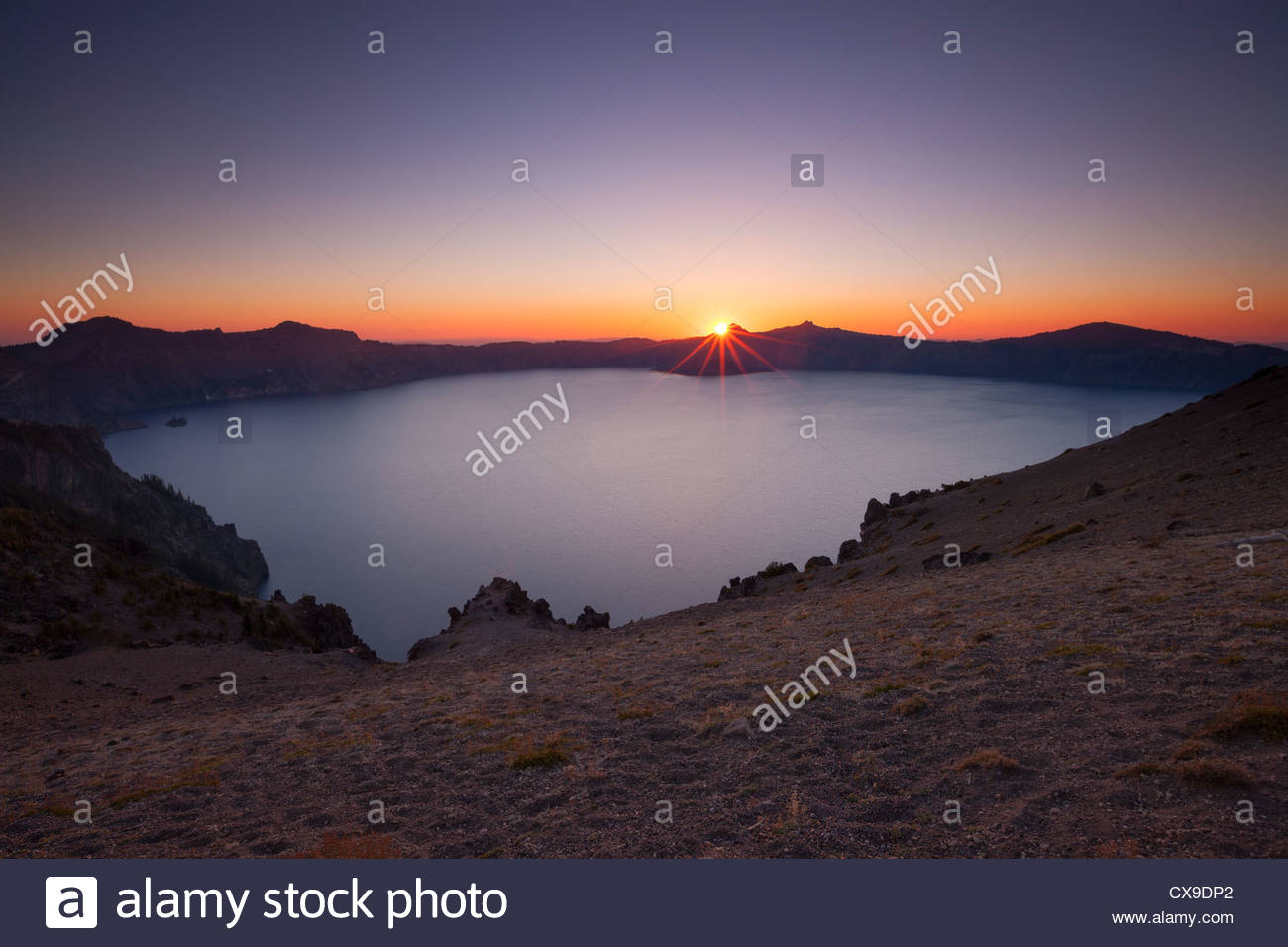 The sun sets behind the rim of Crater Lake in this view from the Cloud Cap Overlook in Crater Lake National Park, - Stock Image
