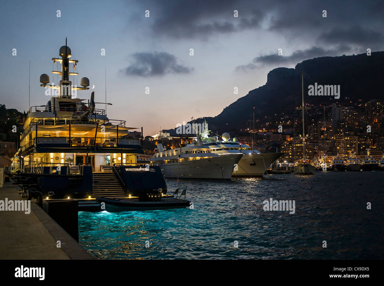 Dusk in Port Hercule, Monaco, with crescent moon above the superyacht on the left. - Stock Image