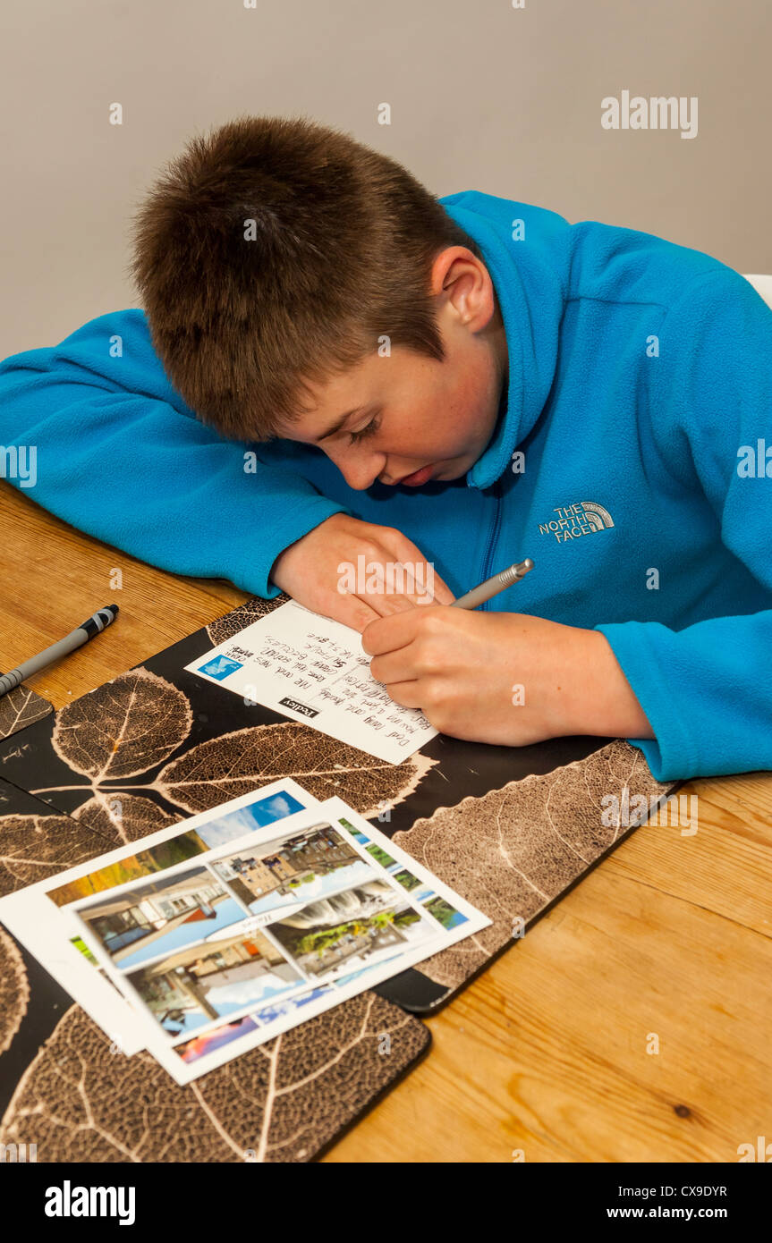 A 12 year old boy writing postcards when on holiday - Stock Image