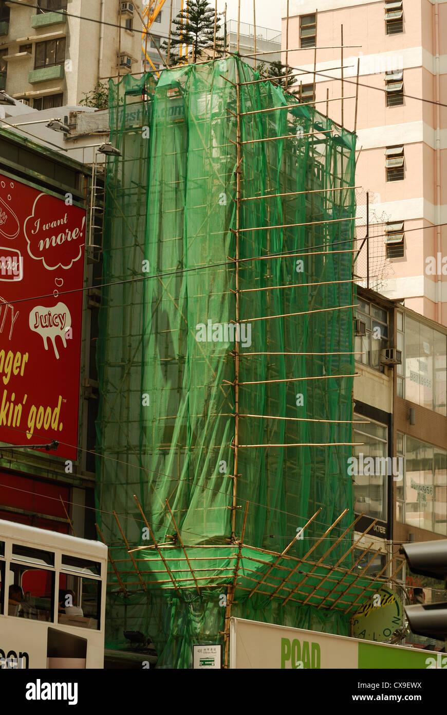 Bamboo scaffolding draped in netting enclose this Hong Kong building. - Stock Image