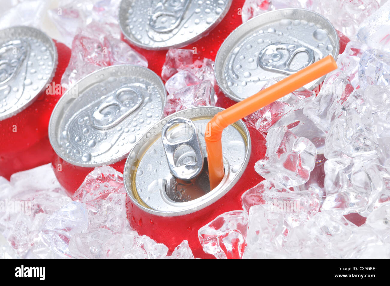 Close Up of Soda Cans in Ice with Straw and Condensation - Stock Image