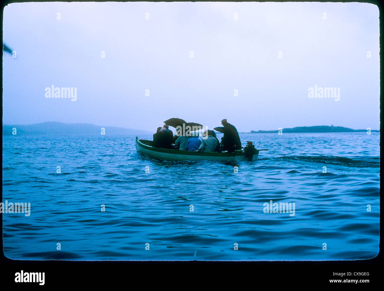 bantry bay whiddy ireland 1969 people in small boat crossing cloudy foggy day europe travel umbrellas - Stock Image