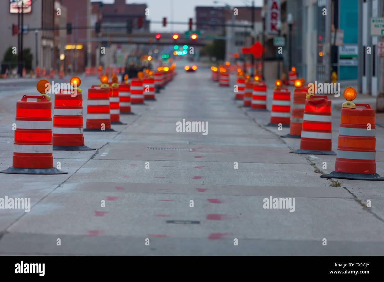 Orange barrels mark a road construction zone in downtown Peoria, IL. - Stock Image
