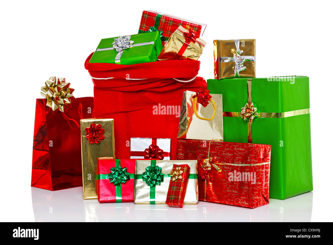 A red Christmas sack full of and surrounded by gift wrapped presents, isolated on a white background. - Stock Image
