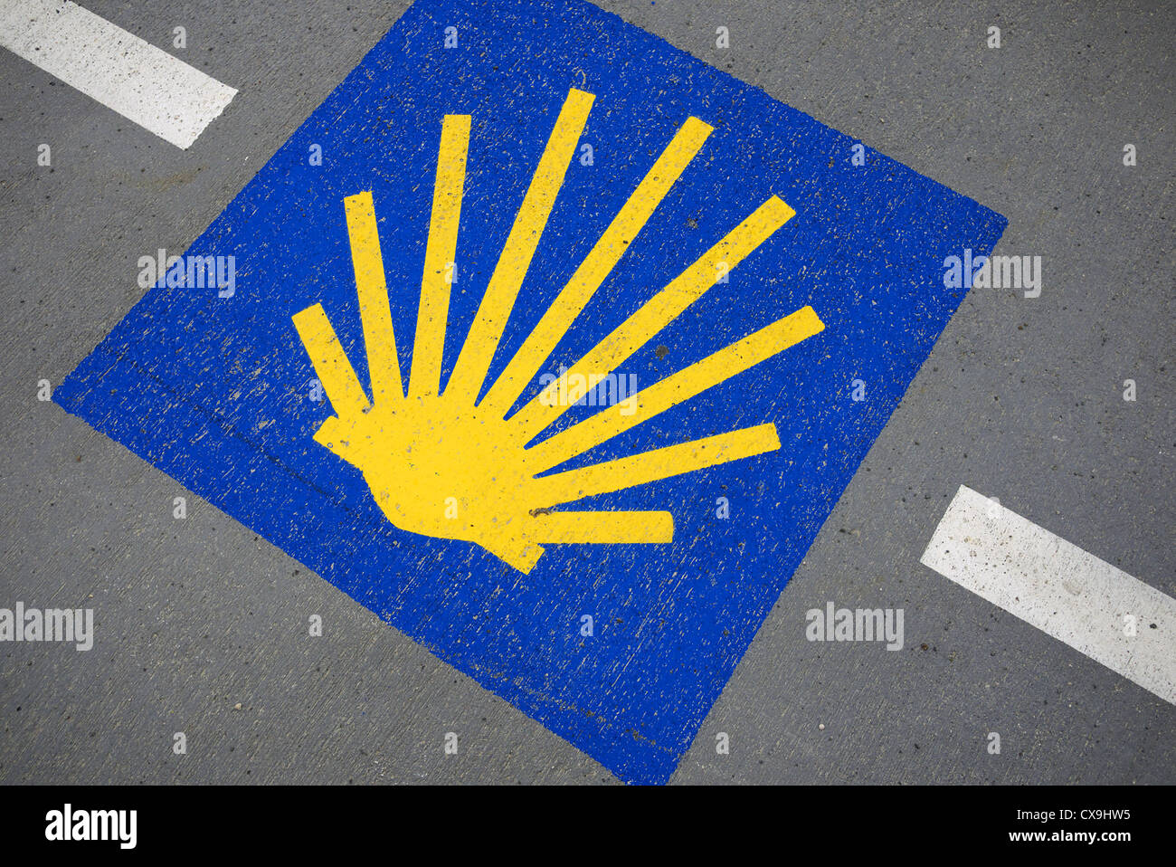 Scallop shell marker for the camino to Santiago painted on the road, Spain. - Stock Image