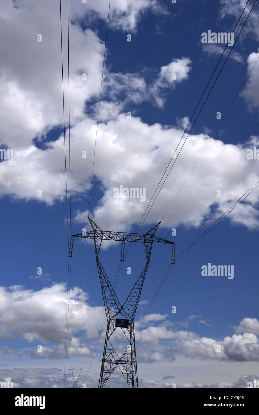 Power lines and pylon against a blue cloudy sky in Spain. - Stock Image