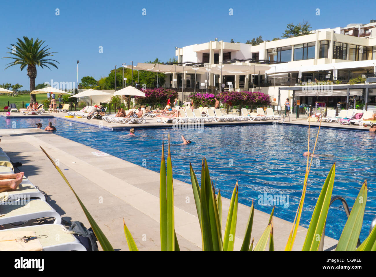 Portugal , Algarve , Club Med , da Balaia , swimming pool surrounded by sun loungers sunbathers & restaurant - Stock Image