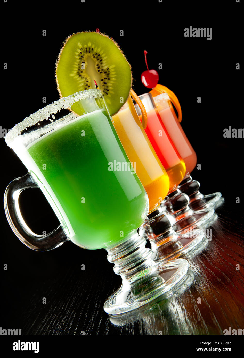 Group of four wine glasses with colored alcoholic cocktails, decorated with fruit and sugar on black bar counter - Stock Image