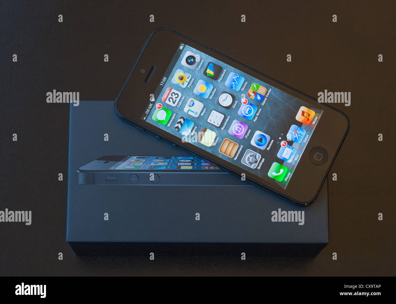 A brand new black Apple iPhone 5 lies on top of it's box - Stock Image